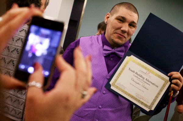 Chris Rubera poses while his mom takes a picture with his diploma after graduating from the Youth Building Alternatives program in Portland Dec. 14, 2012.