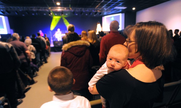 Renee Moran of Brewer holds her eight-week-old daughter, Casey, during the Christmas Eve service at the Rock Church in Bangor Monday.