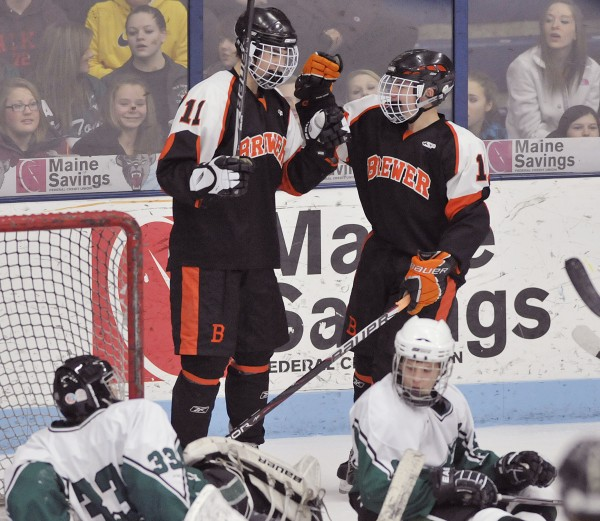 Spencer Valley (11) of the Brewer High School hockey team is congratulated by a teammate after scoring against Old Town in a Jan. 23, 2012, game in Orono. Valley is one of this year's leaders for the Witches, who are off to a 4-0 start in the 2012-13 season.