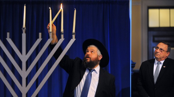 Rabbi Moshe Wilansky lights the third candle on the menorah at the State House in Augusta on Tuesday, Dec. 11, 2012 as Gov. Paul LePage looks on.