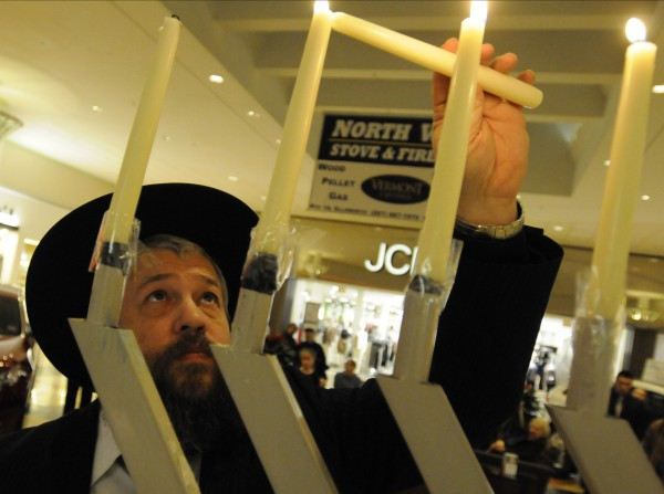 Rabbi Moshe Wilansky of the Chabad Lubavitch of Maine lights the menorah at the Bangor Mall on Tuesday, Dec.11, 2012, the fourth night of Hanukkah.