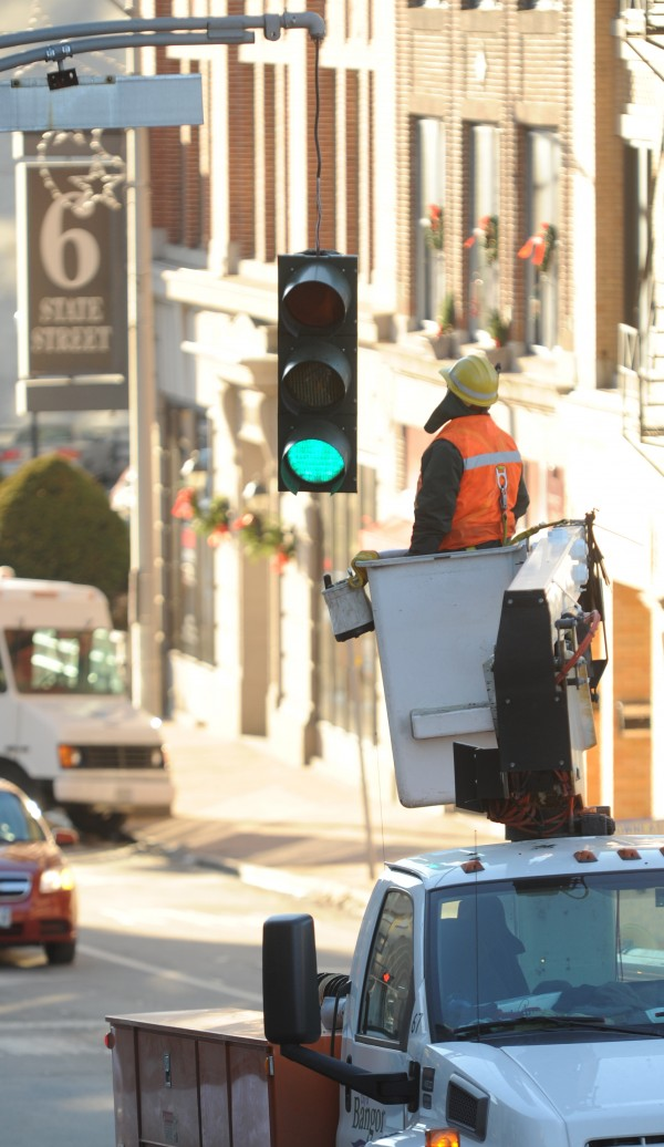 A worker with the city of Bangor prepares to remove a traffic light that was struck by an over-sized load at the bottom of State Street in Bangor on Tuesday, Dec. 11, 2012.