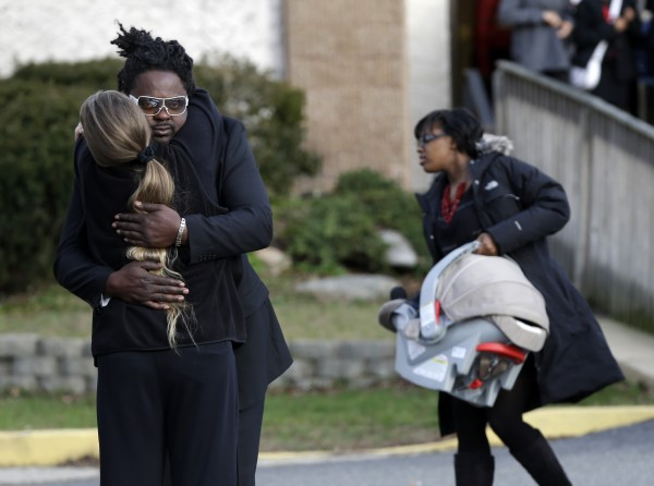 Mourners hug Wednesday after leaving the church where Jovan Belcher's funeral was held in Dix Hills, N.Y. Several hundred mourners gathered for the funeral of Kansas City Chiefs linebacker, who shot and killed his girlfriend and then himself on Dec. 1.