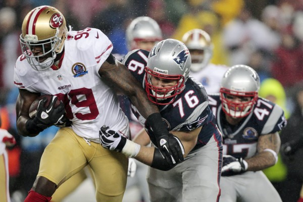 San Francisco 49ers outside linebacker Aldon Smith (99) runs after intercepting a pass as New England Patriots tackle Sebastian Vollmer (76) and tight end Michael Hoomanawanui (47) pursue in the third quarter of an NFL game in Foxborough, Mass., Sunday night, Dec. 16, 2012.