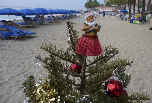 A hula Santa sits on top of a decorated Christmas tree along Waikiki Beach in Honolulu, Hawaii, on Christmas Day, Dec. 25, 2012. It is the 14th year in a row that this hula Santa has been on the beach on Christmas.