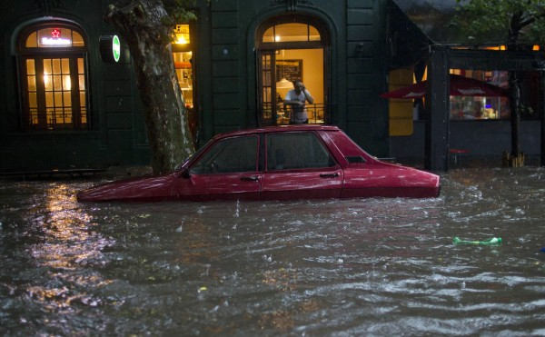 A car is submerged in flood water in front of a home in Buenos Aires, Argentina, on Thursday, Dec. 6. Heavy rain flooded the capital on Thursday.