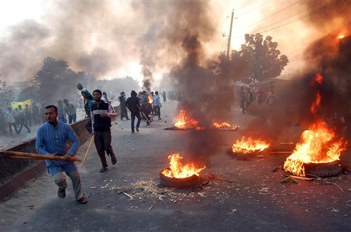 Bangladesh's largest Islamic party Jamaat-e-Islami activists block a road with burning tires during a nationwide strike on the outskirts of Dhaka, Bangladesh, Tuesday, Dec. 4, 2012. The opposition Jamaat-e-Islami party called the strike to demand authorities halt trials of its top leaders on charges of crimes against humanity during the 1971 independence war against Pakistan.