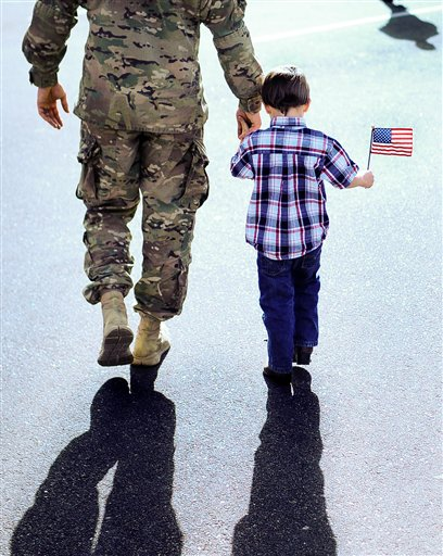 First Lt. Chris Pinkerton walks to get his bags with his son Shawn Pinkerton, 4, after returning home from Afghanistan with 270 of his fellow soldiers from the 4th Brigade Combat team at the Fort Carson Special Events Center in Colorado Springs, Colo. Monday, Dec. 3, 2012.