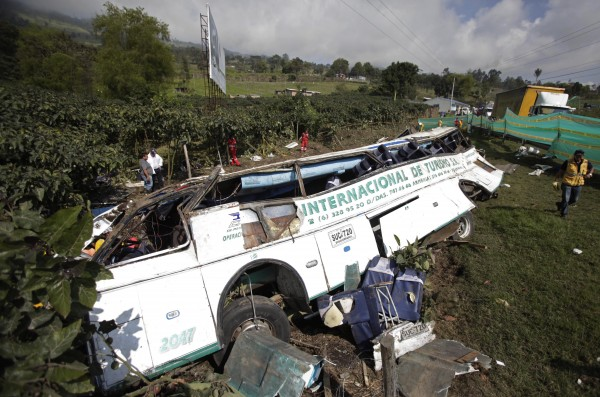 A charter bus that was in an single-vehicle accident lies on its side, in San Raimundo, near Bogota, Colombia, Monday, Dec. 17, 2012. The accident resulted in the death of at least 26 passengers and another 15 wounded. The driver, who survived the accident, told police the brakes failed when he tried to negotiate a curve in the road, causing the bus to swerve off the road and flip over. The bus was part of a convoy transporting the passengers to Cali and Palmira after their visit to a coffee fair in Bogota.
