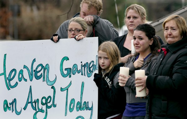 Tom Doyle (back left) standing with family and co-workers, wipes his face as the funeral procession for 6-year-old James Mattioli, who died in the Sandy Hook Elementary School shootings, approaches the St. John's Cemetery on Tuesday, Dec. 18, 2012, in Darien, Conn. Center are his wife Debbie and daughter Emily, 10. Adam Lanza opened fire at the Sandy Hook Elementary School in Newtown on Friday, killing 26 people, including 20 children.