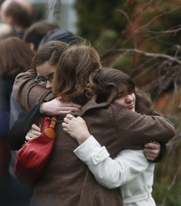 Mourners hug each other before a funeral service for 6-year-old Noah Pozner, Monday, Dec. 17, 2012, in Fairfield, Conn. Pozner was killed when a gunman walked into Sandy Hook Elementary School in Newtown, Conn., Friday and opened fire, killing 26 people, including 20 children.