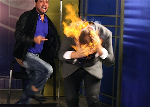 In this picture released by American magician Wayne Houchin, Dominican TV presenter Franklin Barazarte, left, reacts as Houchin's head burns while taping &quotCloser To The Stars&quot TV program in Santo Domingo, Dominican Republic, Monday, Nov. 26, 2012. Houchin, of Chico, California, is receiving treatment for burns after the incident where Barazarte lit his head on fire with a flammable cologne.