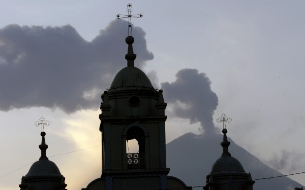 Church steeples are silhouetted against the active Tungurahua volcano, seen from Huambalo, Ecuador, Monday, Dec. 17, 2012. The country's National Geophysics Institute says that a constant plume of gas and ash is rising about half a mile above the crater, with ash falling on nearby communities.