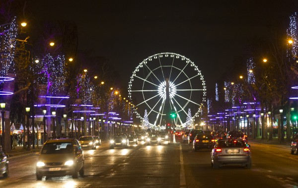 The traffic moves along the Champs Elysees looking towards the Place de la Concorde, Thursday, Dec 6, in Paris. Trees are lit — along with a Ferris wheel — in the Tuileries gardens for Christmas.