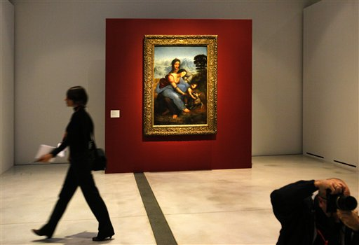 A woman walks past &quotLa Vierge, l'Enfant Jesus et Sainte Anne&quot by Leonard da Vinci in the Louvre Museum in Lens, northern France, Monday, Dec. 3, 2012. The museum in Lens, to open Dec. 12, is part of a strategy to spread art beyond the traditional bastions of culture in Paris.