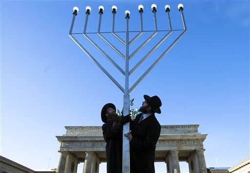 Rabbi Yehuda Teichtal (right) and Rabbi Segal Shmoel install a giant Hanukkah Menorah, at the Pariser Platz in front of the Brandeburg Gate in Berlin, Friday, Dec. 7, 2012. The eight day Jewish Festival of Lights, Hanukkah will start on Dec. 8.
