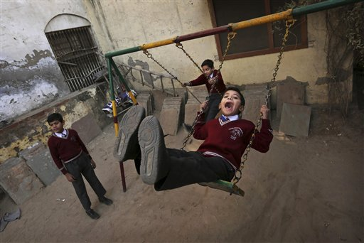 Young Indian students play on a swing after morning assembly at the Central Baptist Church School in New Delhi, India on Friday, Dec. 7, 2012. Built in 1814, the church is one of Delhi's oldest and stands on the historic Chadni Chowk Road.