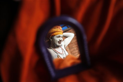 A Naga sadhu, or naked Hindu holy man, reflected on a mirror, ties his turban after taking a holy dip in the River Ganges during preparations for the upcoming over-a-month-long Mahakumbh fair in Allahabad, India, Monday, Dec. 3, 2012. Millions of Hindu pilgrims are expected to take part in the largest religious congregation on the banks of Sangam, the confluence of rivers Ganges, Yamuna and mythical Saraswati, during the festival in January 2013, which falls every twelfth year.