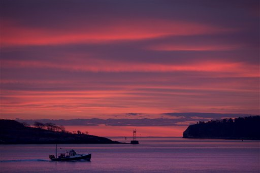 A lobster boat heads out to sea at dawn, Friday, Dec. 7, 2012, of South Portland. A red sky in the morning often indicates a storm system is moving east. Weathermen are calling for showers by the afternoon.