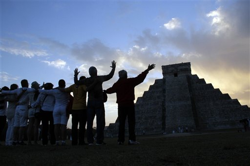 People gesture toward the the Kukulkan temple in Chichen Itza, Mexico on Friday, Dec. 21, 2012. Ceremonial fires burned and conches sounded off as dawn broke over the steps of the main pyramid at the Mayan ruins of Chichen Itza on Friday, making what many believe is the conclusion of a vast, 5,125-year cycle in the Mayan calendar. Some have interpreted the prophetic moment as the end of the world. The hundreds gathered in the ancient Mayan city, however, said they believed it marked the birth of a new and better age.