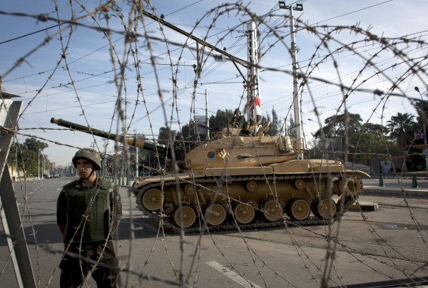 An Egyptian army soldier stands guard next to a tank behind barbed wire securing the perimeter of the presidential palace while protesters, unseen on the other side, chant anti-President Mohammed Morsi slogans, in Cairo, Egypt, on Thursday, Dec. 6. The Egyptian army deployed tanks and gave both supporters and opponents of Mohammed Morsi a deadline to leave the area outside the presidential palace Thursday following fierce street battles that left several people dead and hundreds injured in the worst outbreak of violence between the two sides since the Islamist leader's election.