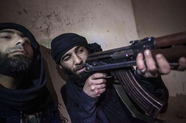 A Free Syrian Army fighter aims his weapon during heavy clashes with government forces in Aleppo, Syria, on Wednesday, Dec. 6.
