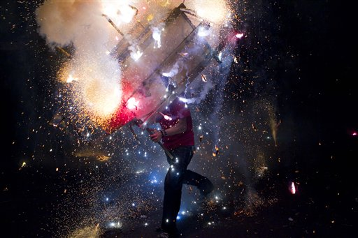 A man runs with &quottoro encuetado,&quot a structure resembling a bull and covered in exploding firecrackers, as part of celebrations in honor of the Virgin Mary of the Immaculate Conception in Managua, Nicaragua, early Saturday, Dec. 8, 2012. Nicaragua's patron saint is the Virgin Mary of the Immaculate Conception, whose feast day is Saturday.