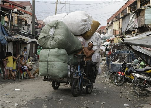 A Filipino man negotiates his motorized bicycle along a dirt road as he brings loads of used plastics which he will sell at a junk shop in a poor district in Manila, Philippines, on Monday Dec. 3, 2012. Many survive on odd jobs in poor communities in the country, where nearly a third of the 90 million population wallow in poverty.