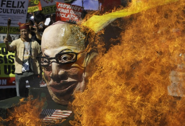 Protesters burn an effigy of Philippine President Benigno Aquino III on board a mock tank as they commemorate International Human Rights Day near the Presidential Palace in Manila, Philippines, on Monday, Dec. 10, 2012. The group called the Aquino administration as alleged human rights violators.