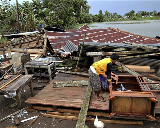 Residents prepare to assess their house, which was damaged by Typhoon Bopha in Butuan city in southeastern Philippines, Tuesday, Dec. 4, 2012. A Philippine governor says at least 33 villagers and soldiers have drowned when torrents of water dumped by the powerful typhoon rushed down a mountain, engulfing the victims and bringing the death toll from the storm to about 40.
