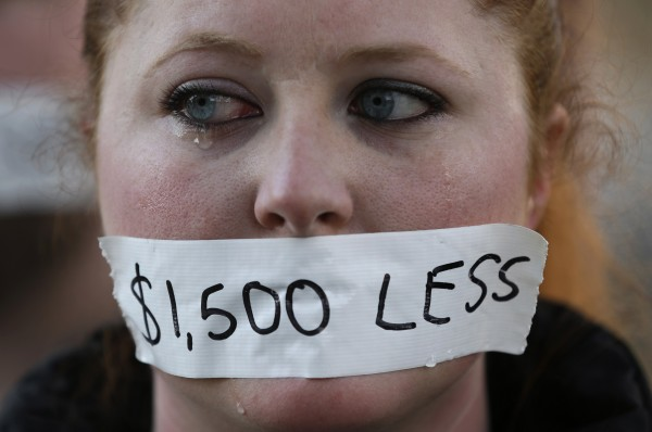 A silent protester cries while wearing a sticker over her mouth signifying the loss in wages from the right-to-work law in Lansing, Mich., Wednesday, Dec. 12, 2012. Michigan became the 24th state with a right-to-work law after Gov. Rick Snyder signed the bill Tuesday.