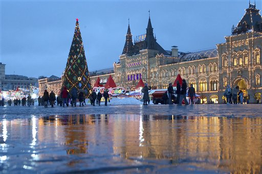 People walk past a Christmas tree in Red Square, with the GUM State Department Store at right, in Moscow, Tuesday, Dec. 4, 2012. A heavy snow fall hit Moscow early morning but it melts in the above-zero temperature.