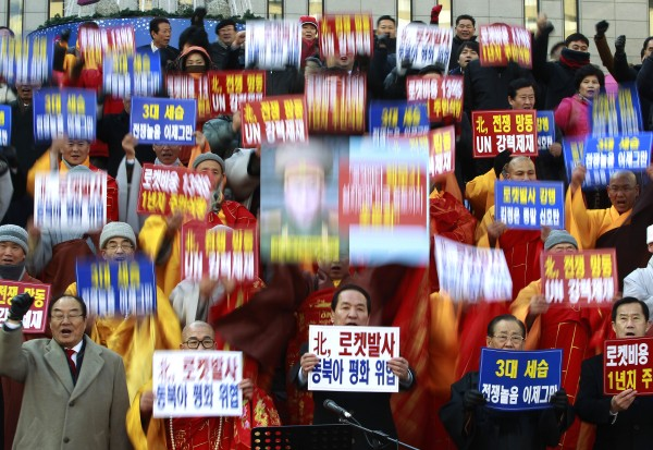 South Korean religious leaders raise placards and shout slogans during a rally denouncing North Korea's rocket launch in Seoul, South Korea, Wednesday, Dec. 12, 2012. North Korea fired a long-range rocket Wednesday in its second launch under its new leader, South Korean officials said, defying warnings from the U.N. and Washington only days before South Korean presidential elections. The words read &quotDenounce North Korea's rocket launch and overthrow family succession through three generations!&quot