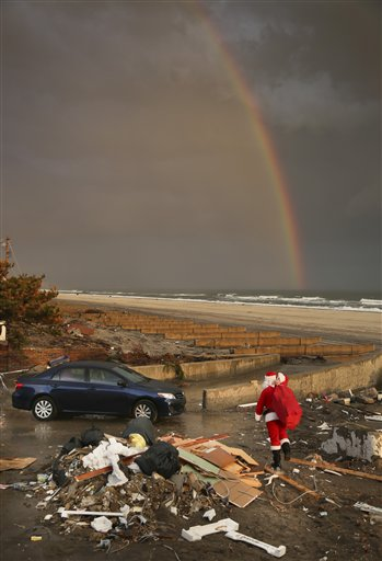 In this Tuesday, Dec. 18, 2012 photo, a rainbow appears as a Santa-dressed Michael Sciaraffo leaves the home of Ella Sampol, 14 months, after bringing her a toy in the Belle Harbor neighborhood of the Queens borough of New York. Using Facebook, Sciaraffo started a charitable enterprise to collect and personally deliver toys to children affected by superstorm Sandy, dressed as Santa Claus.
