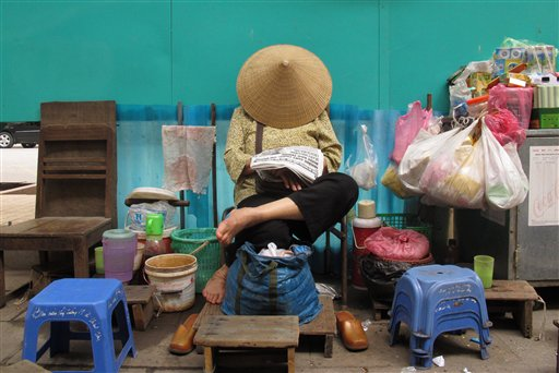 A street vendor sleeps underneath her hat in Hanoi, Vietnam, Friday, Dec. 21, 2012.