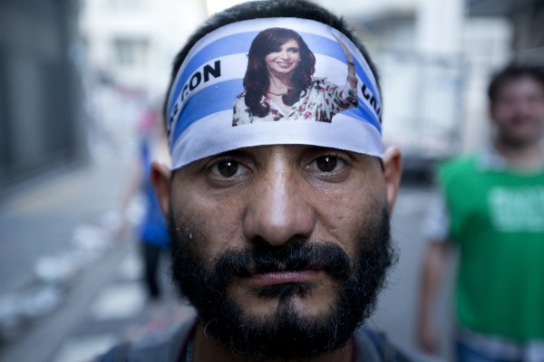 An activist wears a bandana with a photo of Argentine President Cristina Fernandez during a rally to mark the 29th anniversary of the return to democracy in Argentina, on the eve of the Human Rights Day, in Buenos Aires, Argentina,  Sunday, Dec. 9, 2012. Late Argentine President Raul Alfonsin took office on December 10, 1983 after seven years of military dictatorship.