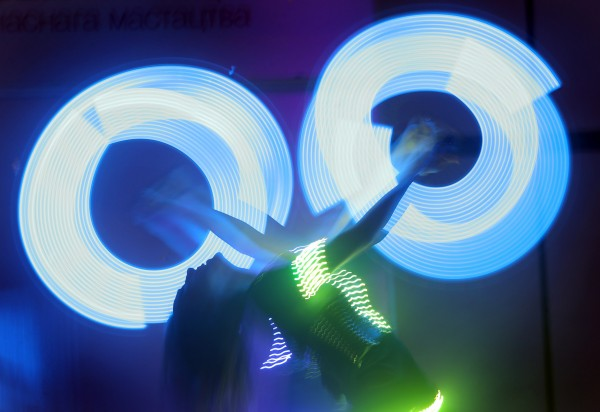 In this photo made with a long exposure, actors perform with neon lamps during the BelExpoArt-2012 exhibition of contemporary Belarusian art in Minsk, Sunday, Dec. 9, 2012.