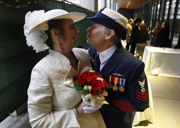 Retired U.S. Coast Guard Petty Officer 1st Class Nancy Monahan, right, wears her dress uniform as she leans to kiss her soon-to-be bride Deb Needham while they wait at Seattle City Hall to become among the first gay couples to legally wed in the state, Sunday, Dec. 9, 2012, in Seattle. The couple is from Renton, Wash. Gov. Chris Gregoire signed a voter-approved law legalizing gay marriage Dec. 5 and weddings for gay and lesbian couples began in Washington on Sunday, following the three-day waiting period after marriage licenses were issued earlier in the week.