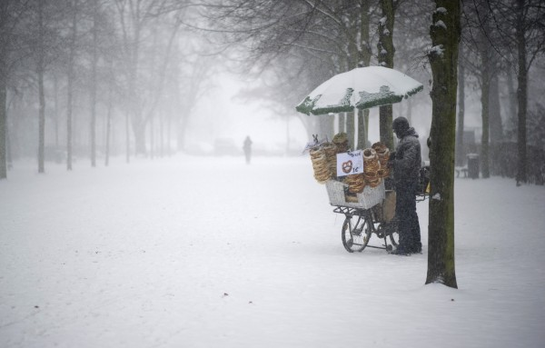 A pretzel vendor waits for customers during heavy snowfall near the Brandenburg Gate, in Berlin, Germany, Sunday, Dec. 9, 2012.