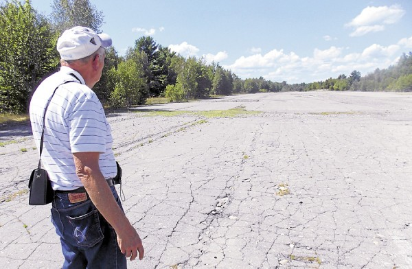 Dr. David Bergquist, a retired college dean, looks at the far end of the abandoned 2,500-foot air strip built east of Milford during World War II. Not many people know that the air strip exists.