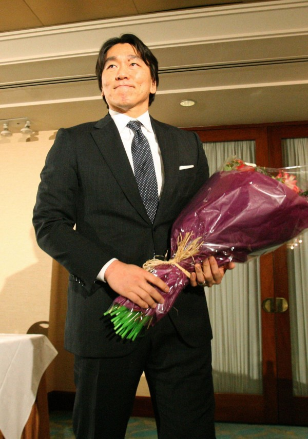 Former New York Yankees player Hideki Matsui holds a bouquet after a news conference to announce his retirement from baseball in New York, in this Kyodo photo taken December 27, 2012. No longer the fearsome, fire-breathing &quotGodzilla&quot of old, injury-ravaged Hideki Matsui retired from baseball with his head held high and as a huge source of national pride for Japan. The 38-year-old slugger, World Series MVP in 2009 with the New York Yankees, helped put Japanese baseball on the map after the trail-blazing Hideo Nomo and mercurial Ichiro Suzuki had enjoyed success across the Pacific. Picture taken December 27, 2012.