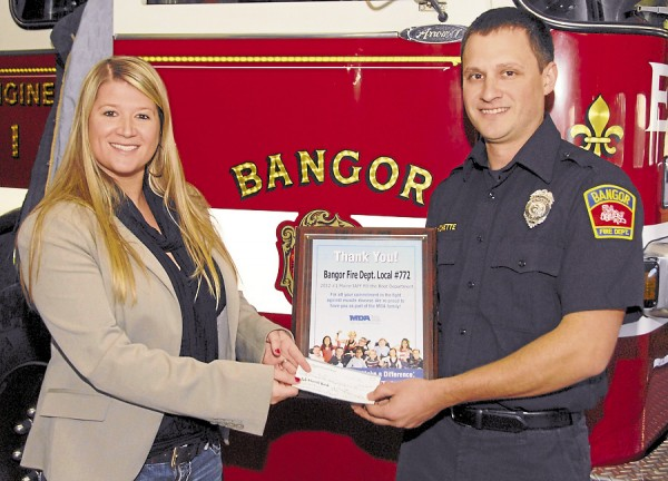 Ashley K. Bolton, executive director of the Muscular Dystrophy Association in Maine, receives a check for $20,580.80 from Ryan Blanchette, a firefighter/paramedic with the Bangor Fire Department. Bangor firefighters raised the funds this year in conjunction with the International Association of Firefighters. According to Blanchette, 2012 was the third year that Bangor firefighters have raised more than $20,000 for the MDA. The check presentation took place on Friday, Nov. 30.