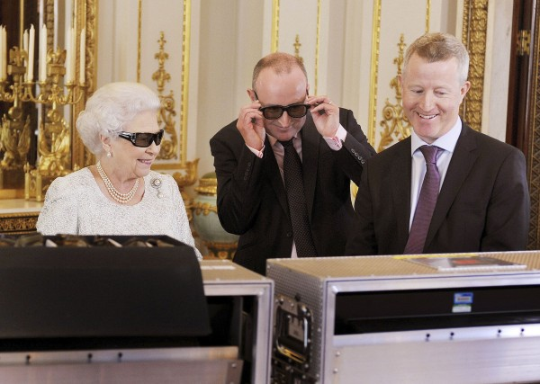 Britain's Queen Elizabeth (left) watches a preview of her Christmas message with a pair of 3D glasses, studded with Swarovski crystals in the form of a &quotQ&quot, with producer John McAndrew and director John Bennett (right), at Buckingham Palace in central London in a photo released Dec. 24, 2012. The Christmas message to the Commonwealth is to be broadcast in 3D for the first time.