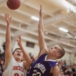 Brewer senior Ian Burgess (24) tries to get a shot over the defense of Hampden Academy player Zachary Gilpin (23) in the first half of their game in Brewer, Maine, Friday, Dec. 28, 2012. Hampden downed the Witches 66-46.