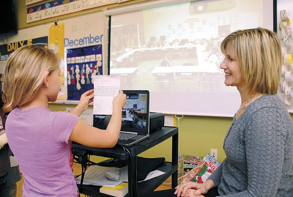 Brewer Community School teacher Cherrie MacInnes watches as third-grader Anna displays a photo and discusses it while video-chatting with a third-grade class at a public school in Lake Ariel, Penn. in mid-December.