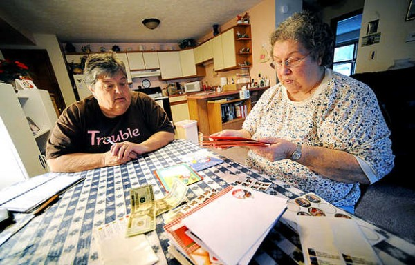 Marge Chaplin, left, helps out her neighbor, Betty Lugner, who has Parkinson's disease, by writing out Lugner's Christmas cards Monday in Auburn. On Friday, Lugner was the victim of a phone scam saying her grandson would be jailed in Mexico if she didn't send cash.