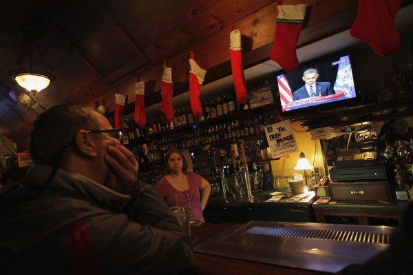 A patron and a bartender watch U.S. President Barack Obama speak during a vigil on a television at Church Hill restaurant in Newtown, Conn., on Sunday, Dec.16, 2012.