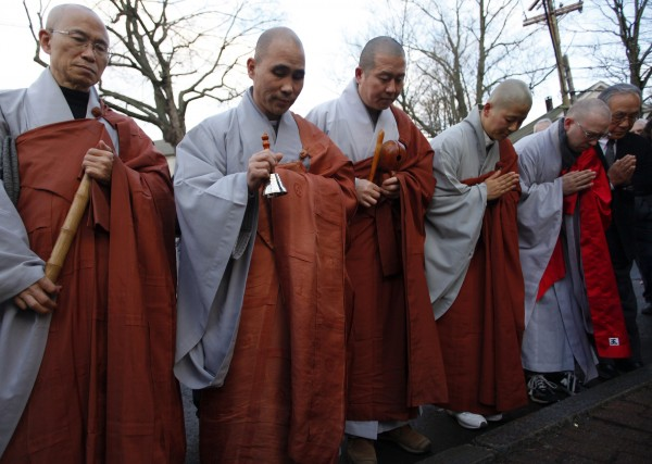 Buddhist monks pray for the victims of Sandy Hook Elementary School shooting at a memorial in Newtown, Conn., on Dec. 18, 2012. U.S. authorities continue to investigate the Dec. 14 massacre in Connecticut in which a heavily armed gunman entered Sandy Hook Elementary school and shot and killed 20 children and six adults.