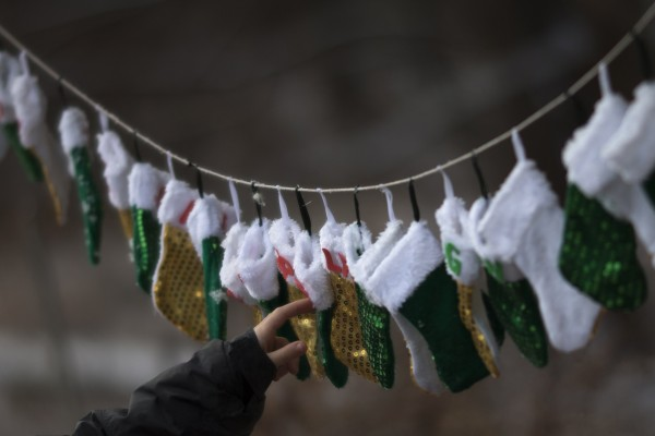 A boy touches stockings, representing those killed in the Dec. 14 shootings at Sandy Hook Elementary School, on Christmas morning in Sandy Hook Village in Newtown, Conn., Dec. 25, 2012.