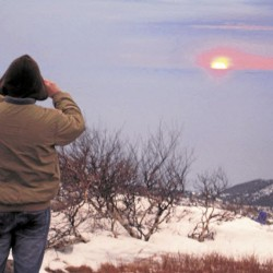 A hiker photographs the New Year's Day from atop Cadillac Mountain in Acadia National Park.